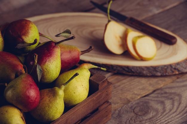木製の背景に木製の箱に葉を持つ新鮮な梨。