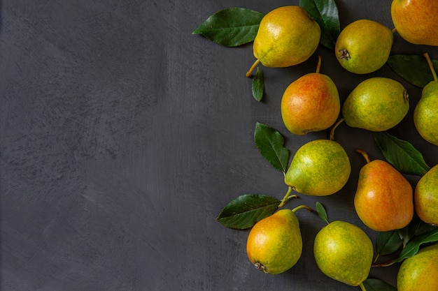 Fresh pears with leaves lie on a gray table