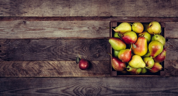 Fresh pears with leaves in a wooden box on wooden background.
