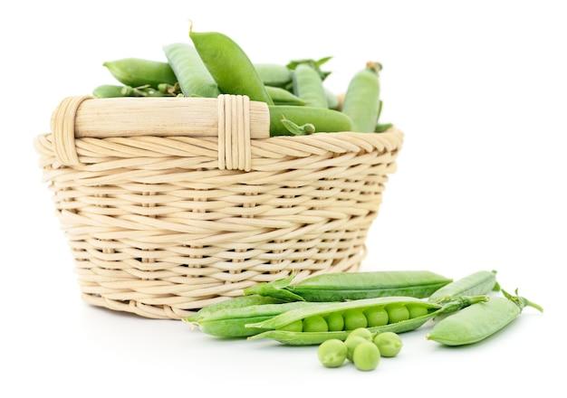 白い背景の上のバスケットの新鮮なエンドウ豆。