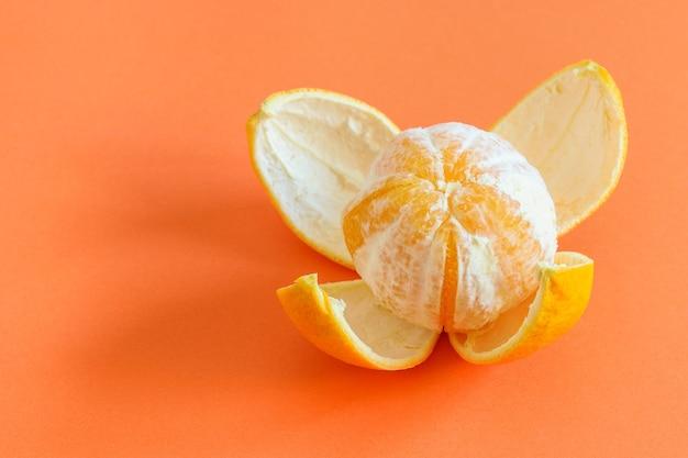 Свежий очищенный апельсин на фоне кораллов, приготовленный для еды. здоровая фруктовая диета.