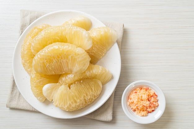 흰 접시에 신선한 껍질을 벗긴 포멜로, 자몽 또는 shaddock