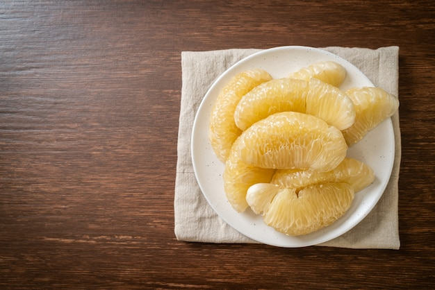 Fresh peeled pomelo, grapefruit or shaddock on white plate