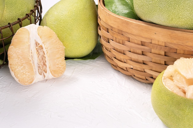明るい木製のテーブルの背景に新鮮な皮をむいたザボン、ザボン、グレープフルーツ、シャドック。中秋節の季節のフルーツ、クローズアップ、コピースペース。