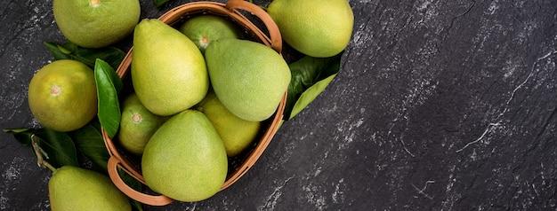 新鮮な皮をむいたザボン、ザボン、グレープフルーツ、竹かごの暗い背景にシャドック。秋の季節のフルーツ、トップビュー、フラットレイ、卓上ショット。