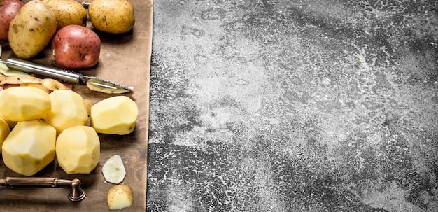 古いトレイに新鮮な皮をむいたジャガイモ。素朴なテーブルの上。