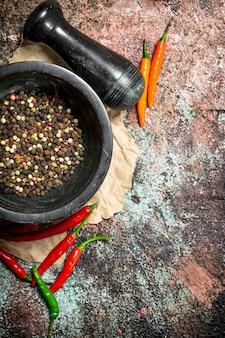 素朴なテーブルのポッドに乳棒と唐辛子を入れた乳鉢の新鮮なペッパーエンドウ豆