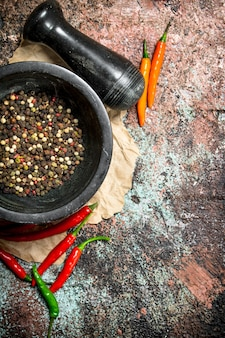 Fresh pepper peas in a mortar with pestle and hot pepper in a pod on rustic table