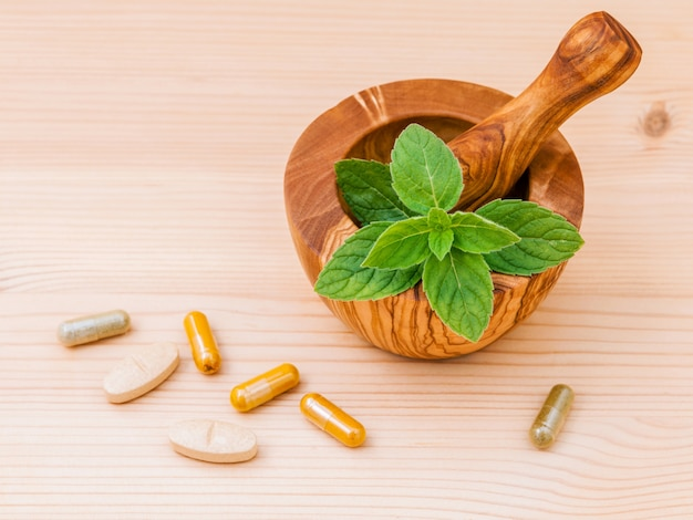 Fresh  peppermint leaves wooden mortar  and capsule of herbal medicine .