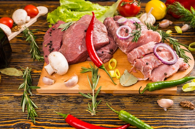 Fresh peppers of various types and color with raw meat chunks on cutting board next to rosemary sprigs, lettuce, tomato, mushrooms and garlic