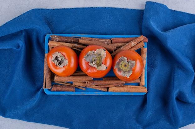 Свежие фрукты хурмы и палочки корицы на голубой тарелке.
