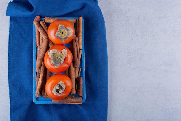 Свежие фрукты хурмы и палочки корицы на синей тарелке.