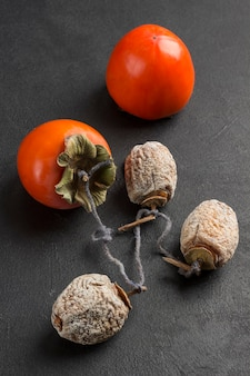 Fresh persimmons and dried persimmons on black background