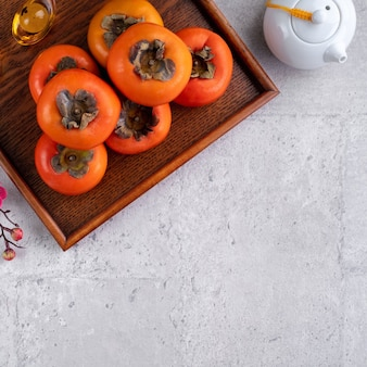 Fresh persimmons on gray table background for chinese new year fruit design, words on the golden coin means the dynasty name it made.
