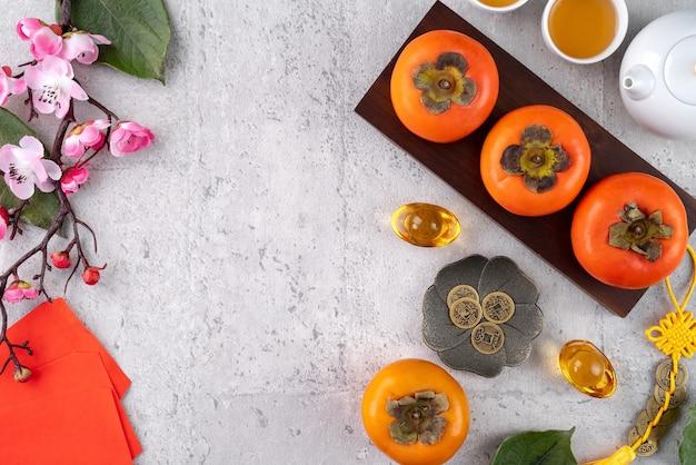 中国の旧正月の果物のデザインの灰色のテーブルの背景に新鮮な柿、黄金のコインの言葉はそれが作った王朝の名前を意味します。