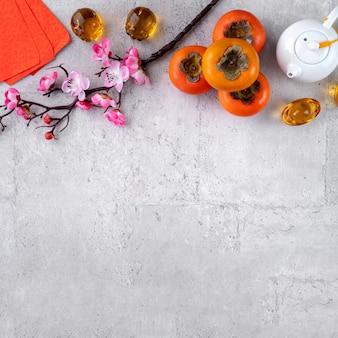 Свежая хурма на сером фоне стола для китайского новогоднего фруктового дизайна, слова на золотой монете означают название династии, которое она сделала.