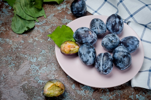 Fresh picked plums in ceramic plate on dark surface
