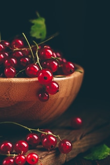 Fresh picked red currants in wooden bowl