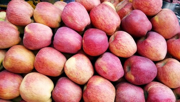 수확철에 갓 고른 붉은 꿀 바삭한 사과 배경이 시장이나 시장에 판매된다