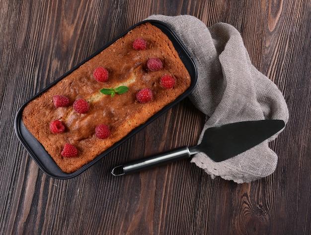 木製のテーブル、上面図の鍋にラズベリーと新鮮なパイ