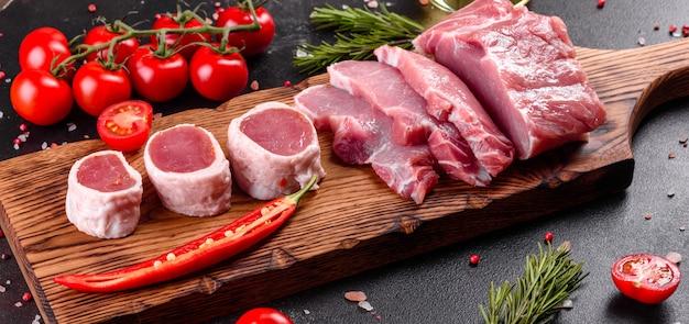 Свежие кусочки свинины готовы приготовить. филе медальонов в стейках в ряд готовых готовить