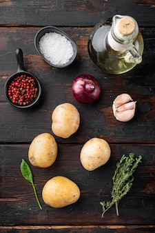오래된 짙은 나무 테이블 배경에 있는 신선한 감자 더미, 평면도