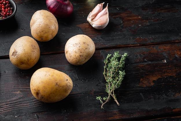 오래된 어두운 나무 테이블에 있는 신선한 감자 더미