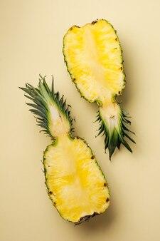 Свежий ананас разрезать на две части и бумажную рамку на желтом фоне. летняя концепция. творческая плоская планировка с копией пространства. вид сверху.
