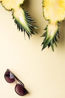 Свежий ананас разрезать на две части, блокнот или альбом для рисования и солнцезащитные очки на желтом фоне. летняя концепция. творческая плоская планировка с копией пространства. вид сверху.