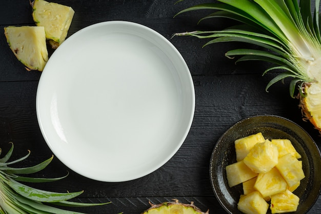 Fresh pineapple on dark wooden surface