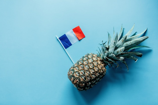 Fresh pineapple and french flag on blue background. above view