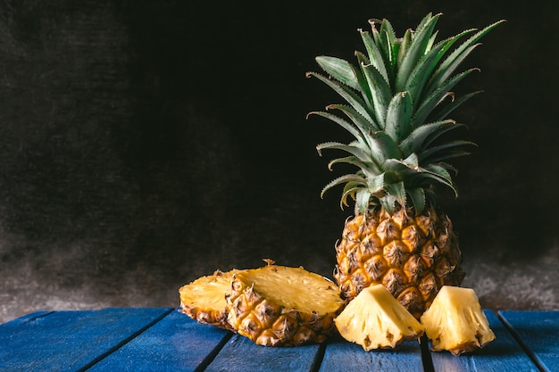 Fresh pineapple fruit on blue wooden table with black background. copy space