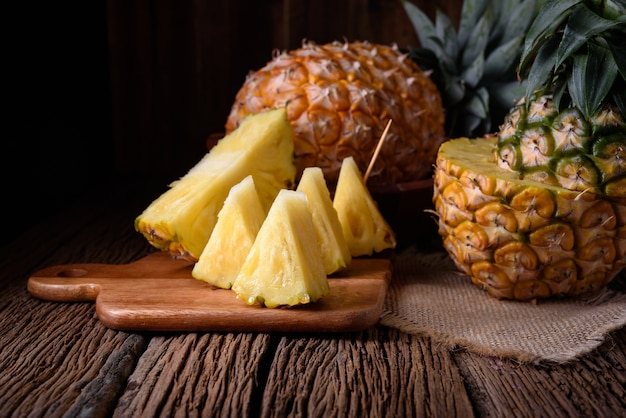 Fresh pineapple and juice on wooden table.