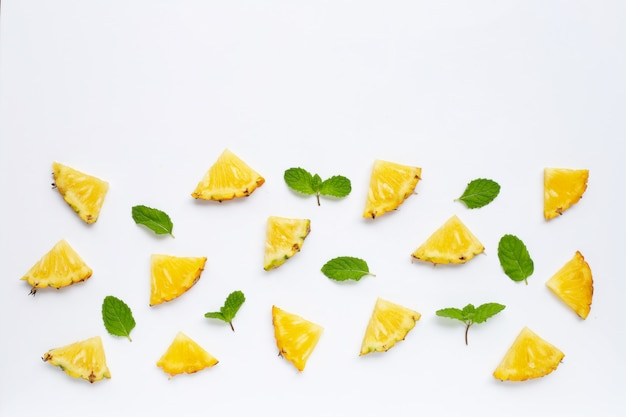Fresh pineapple pieces with green mint leaves