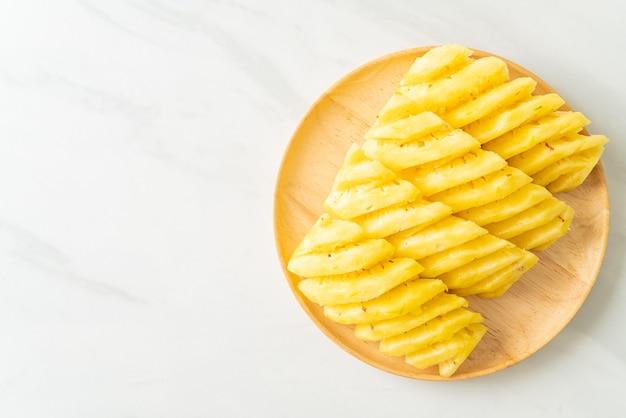 Свежий ананас, нарезанный на деревянной тарелке