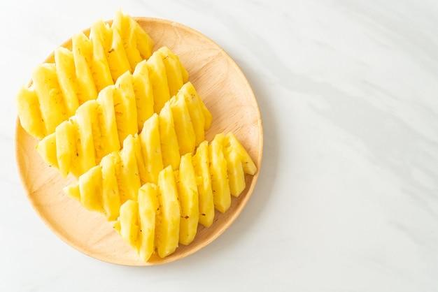 Fresh pineapple sliced on wooden plate