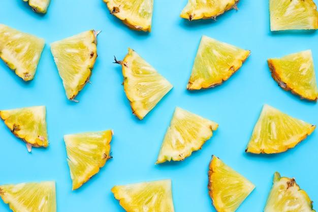 Fresh pineapple slices on blue pattern.