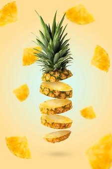 黄色の背景にピースと一緒に飛んでいる新鮮なパイナップルスライス。創造的な食品のコンセプト。