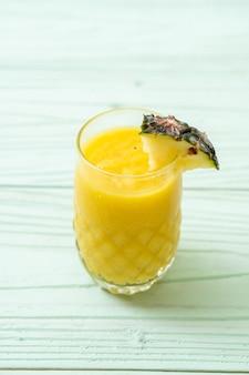 Стакан свежего ананасового смузи на деревянном столе - здоровый напиток