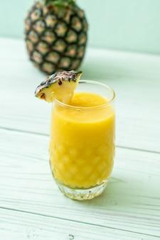 木のテーブルに新鮮なパイナップルのスムージーグラス