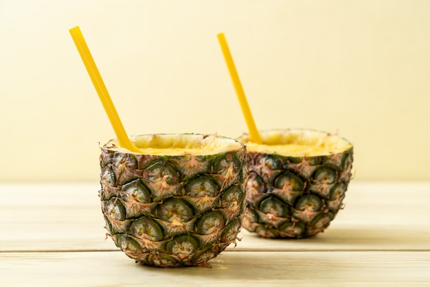 Fresh pineapple smoothie glass on wood table