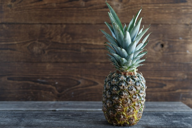 Fresh pineapple on a wooden table with a wooden board