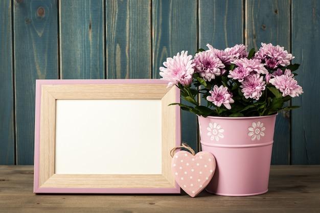양동이, 심장 및 빈 프레임에 신선한 분홍색 국화 꽃