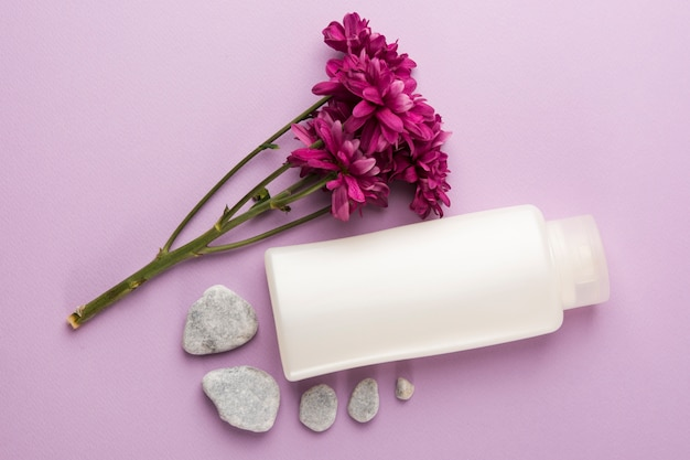 Fresh pink flowers; spa stones and closed bottle on pink background