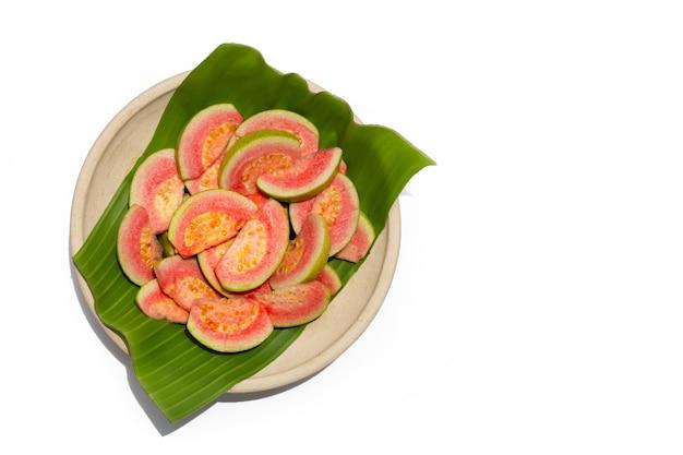 흰색 바탕에 접시에 바나나 잎에 신선한 분홍색 구아바 조각.
