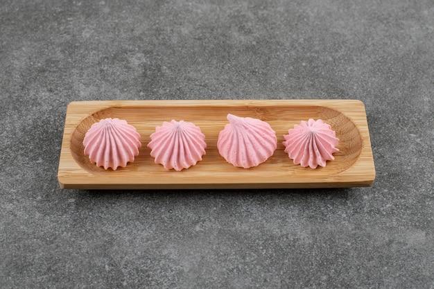 회색 테이블 위에 나무 보드에 신선한 분홍색 머 랭 쿠키.