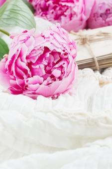 Свежие розовые пионы на белом кружеве