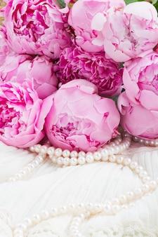 Свежие розовые пионы с жемчугом на белом кружеве