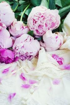 Свежие розовые пионы с лепестками и белое свадебное платье, винтажный стиль
