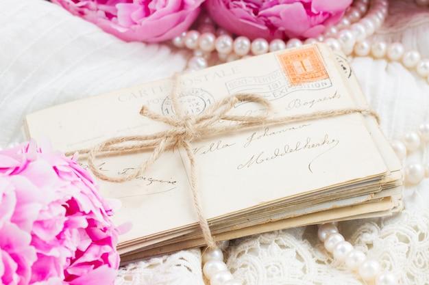 Свежие розовые пионы с кучей старых кольчуг и жемчужных украшений